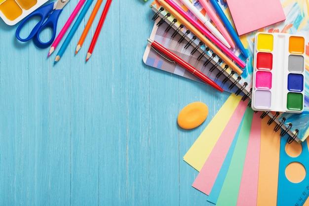 Коллекция школьных принадлежностей на синий деревянный стол