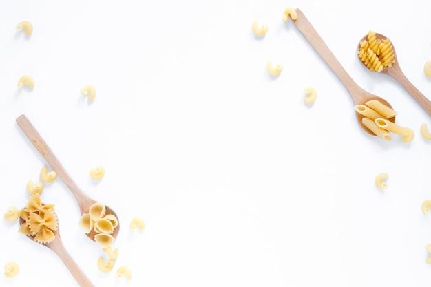 Коллекция ложек, наполненных различными сухими макаронами на белом фоне