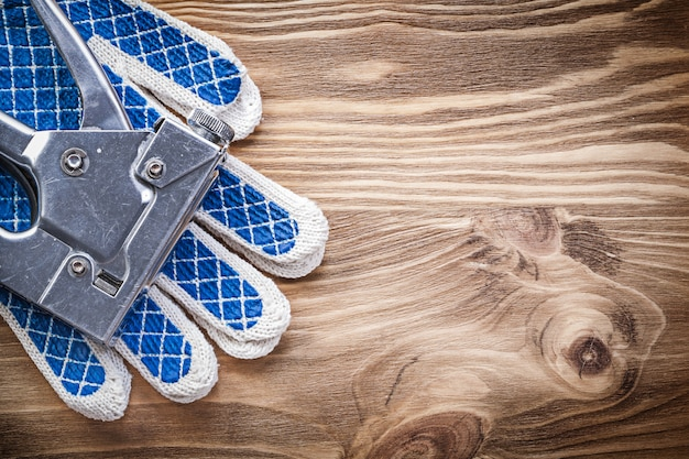 Коллекция скоб и защитных перчаток на деревянной доске