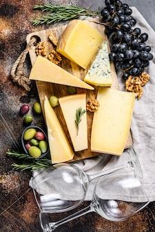 Коллекция швейцарских, голландских, французских, итальянских сыров с орехами и виноградом. темный фон вид сверху