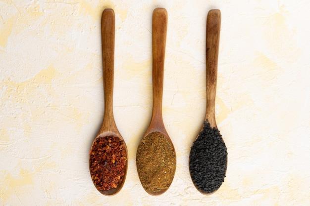 Сбор трех специй на деревянных ложках на желтой поверхности цемента.