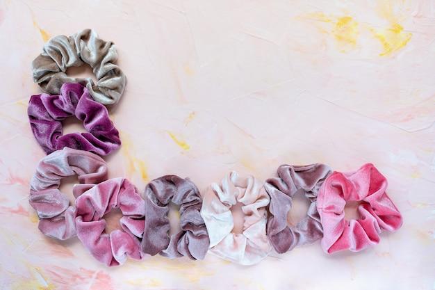 Коллекция модных бархатных резинок для волос на розовом фоне.
