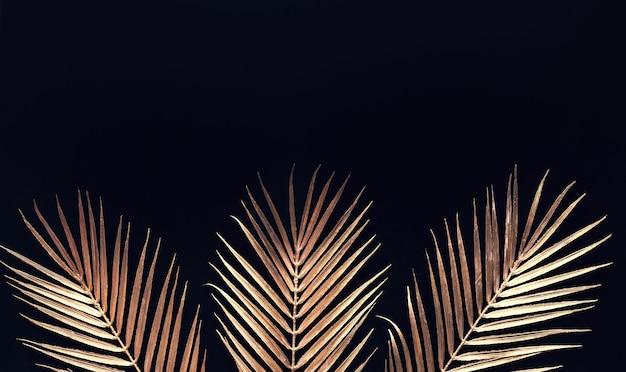 Коллекция тропических листьев золотого цвета на черном космическом фоне. абстрактный дизайн украшения листьев. плоское искусство