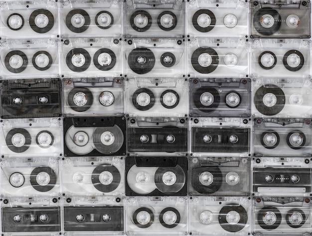 Коллекция различных старинных аудиокассет на белом фоне