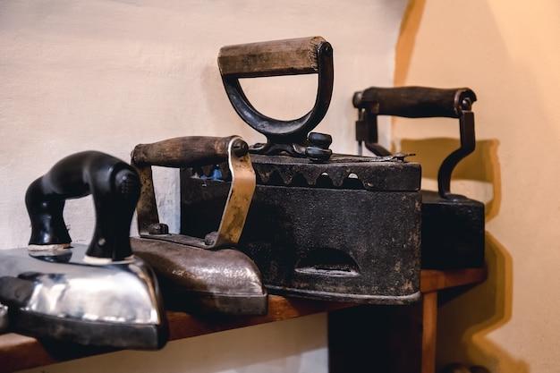 衣類にアイロンをかけるためのビンテージアイロンのコレクション。アンティークの金属製のアイロン、アンティークの家電製品の博物館の作品。コードレスメタルチャコールアイロン。