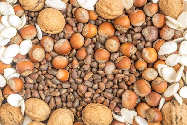 シェルのクルミとヘーゼルナッツのコレクション。松の実とカボチャの種フラットレイと上面図の背景