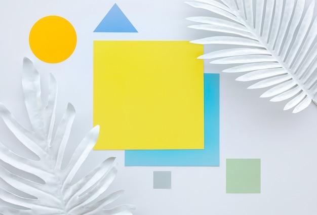 幾何学的な色の背景を持つ白い熱帯の葉のコレクション
