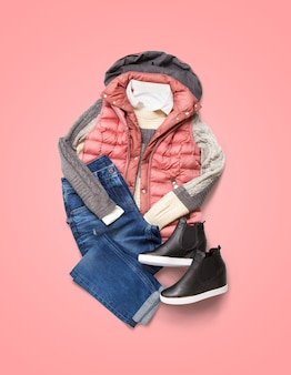 분홍색 배경에 겨울 여성 의류 컬렉션입니다. 재킷, 청바지 및 신발 구성
