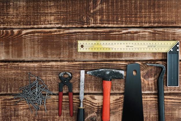 목공, 장인 및 수공 개념, 평면 배치 : 나무 테이블 및 복사 공간에 목공 도구의 컬렉션입니다. 톱, 망치, 끌, 손톱, 자.