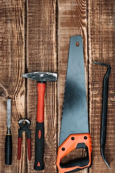 Собрание инструментов woodworking на деревянном столе и космосе экземпляра: плотничество, мастерство и handmade концепция, плоское положение. пила, молоток, зубило, гвозди, линейка.
