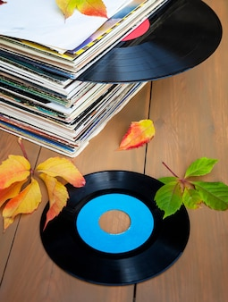 Collection of old vinyl records in a stack with autumn leaves.
