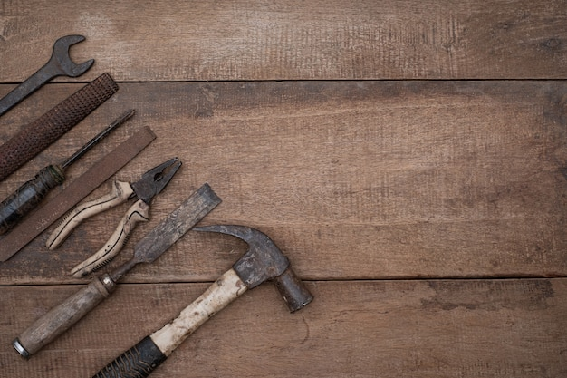 Collection of old woodworking handtools on a rough workbench wooden with copy space