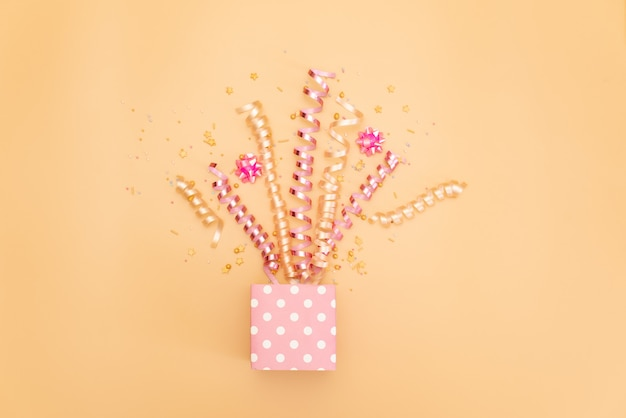 Collection of pink birthday party objects in a gift box
