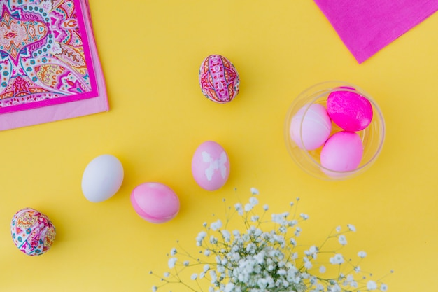 Collection of pink easter eggs in bowl near napkins and flowers