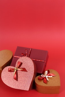 Collection of red and gold valentine gifts on a red paper background.