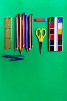 Collection of school supplies from paints, pencils, scissors, ruler, eraser and compasses on green