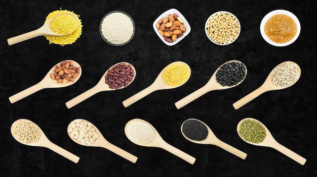 暗い背景、上面図に分離された木のスプーンで豆とゴマのコレクションセット