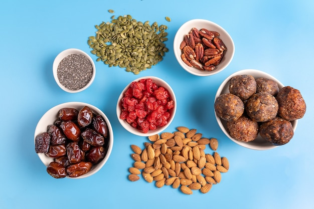 Collection of superfoods and nuts in bowls for health, fitness and vitality used for preparing energy balls. top view. on blue background.