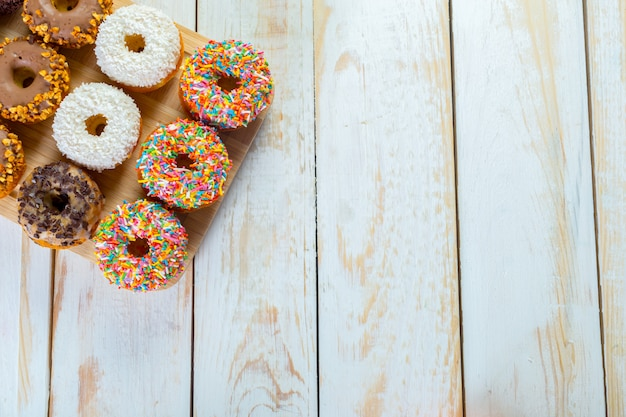 Collection of tasty donuts on white wooden board