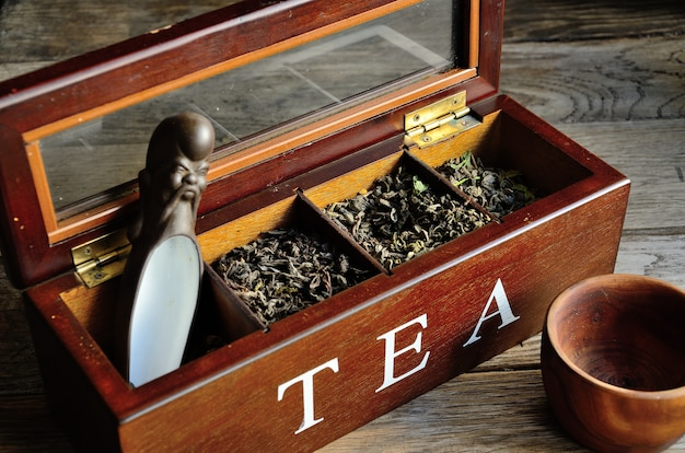 A collection of tea in a wooden box, a wooden glass with a stylized teaspoon on a wooden background.