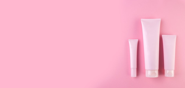 Collection of three cosmetic tubes on pastel pink background. plastic tube with face or body cream on pink. top view, flat lay. long wide banner. copy space for your design.