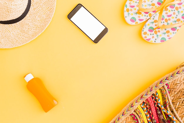 Collection of tropical beach vacation belongings and phone on yellow background
