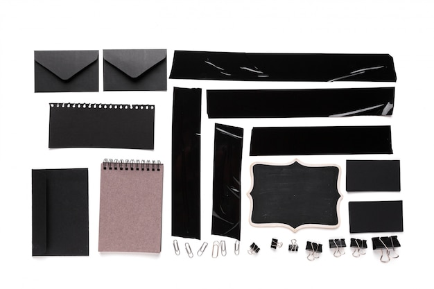 A collection of used black electrical tape pieces with stationery tools for your design