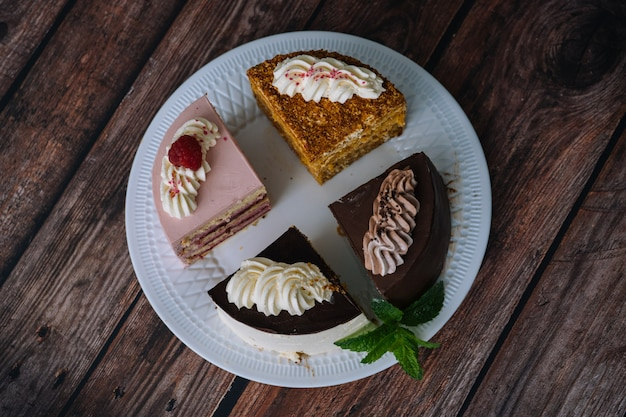 Collection of various cakes on wood table. assortment of pieces slices with cream. plate with different types of sweets. several slices of delicious desserts. confectionery menu concept