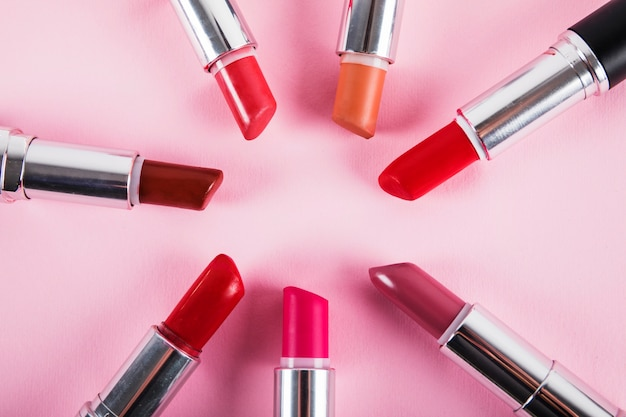 Collection of various colorful lipsticks on pink surface