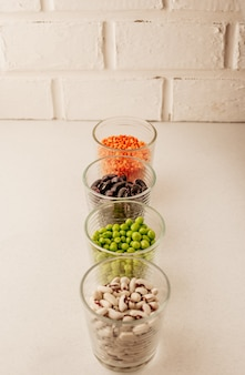 Collection of various dried legumes in glasses
