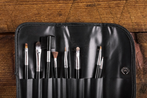 Collection of various makeup brushes on wooden background