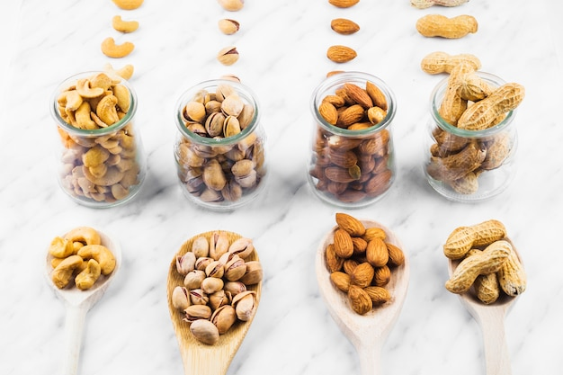 Collection of various nut food in spoon and glass jar on marble surface