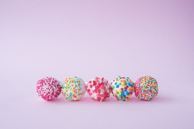 Collection of various round pink lollipops isolated on pink background. sweets in a cartoon style. set of colorful sweets. place for your text.