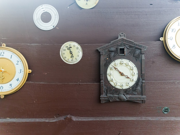 Collection of vintage clock hanging on an old wooden wall on the outdoors with sunshine