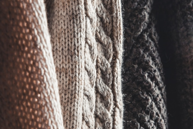 Collection of warm sweaters hanging on rack against graybackground, closeup