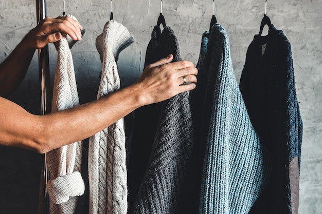 Collection of warm sweaters hanging on rack on gray