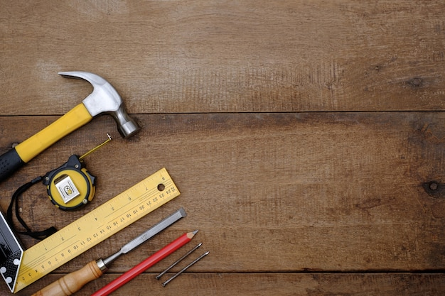 Collection of woodworking hand tools on a rough workbench wooden background with copy space