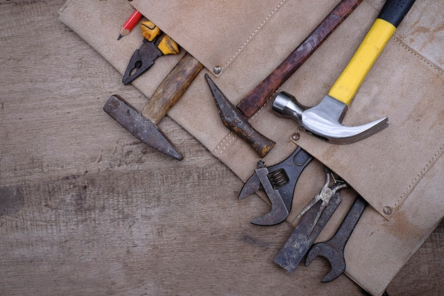 Collection of woodworking old hand tools in leather apron on a rough workbench wooden