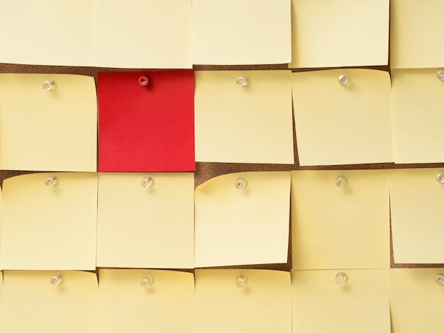 Collection of yellow sticky notes surrounding a red one