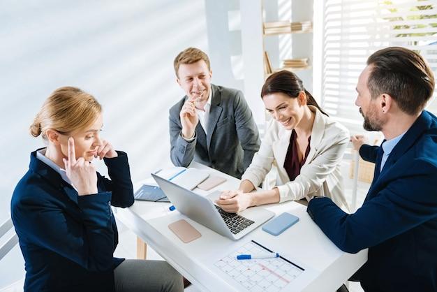 Коллективные усилия. профессиональные молодые четыре коллеги обдумывают проект, совещаясь и улыбаясь