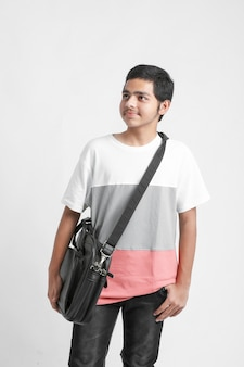 College boy holding schoolbag on white wall