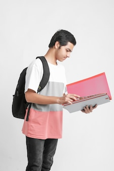 College boy holding with files in hand on white wall