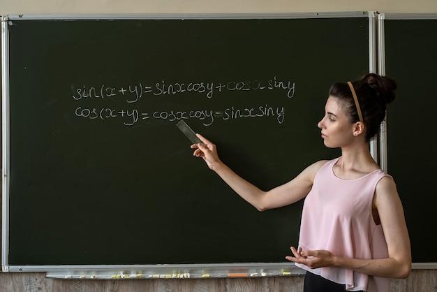 数学の方程式を完成させる黒板に書く大学の女子学生。教育の概念