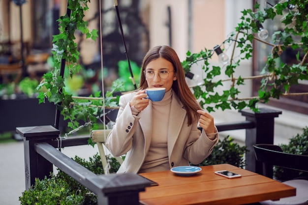 College girl dressed smart casual sitting in cafeteria outdoors and drinking her coffee on a coffee break.