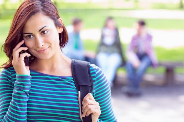 公園でぼんやりした学生と携帯電話を使用している大学の女の子