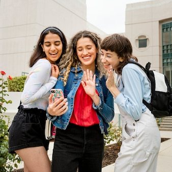 College girls video calling with friends at campus