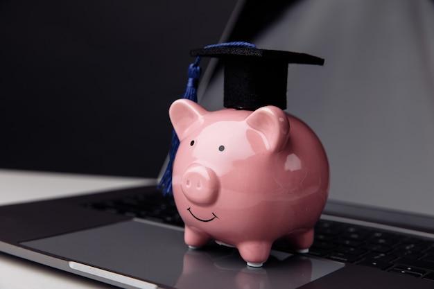 대학, 대학원, 디플로마 개념입니다. 키보드에 모자에 핑크 돼지 저금통입니다. 온라인 교육.