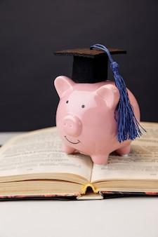 Колледж, выпускник, концепция образования. розовая копилка в кепке остается на книге.