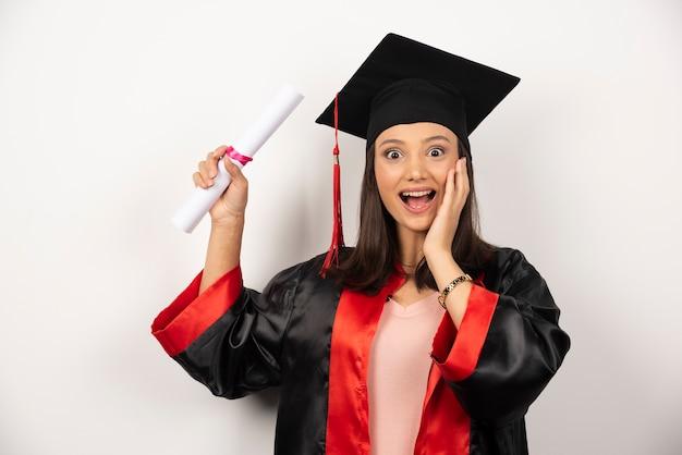 Laureato universitario femminile in abito sentirsi felice su sfondo bianco.