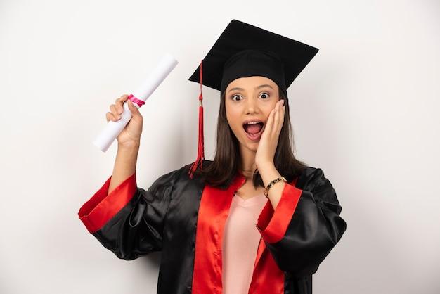 白い背景で幸せな感じのガウンの大学卒業生の女性。